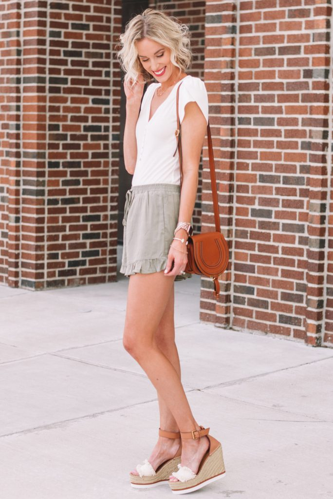 olive ruffle hem pull on shorts styled with a white henley bodysuit
