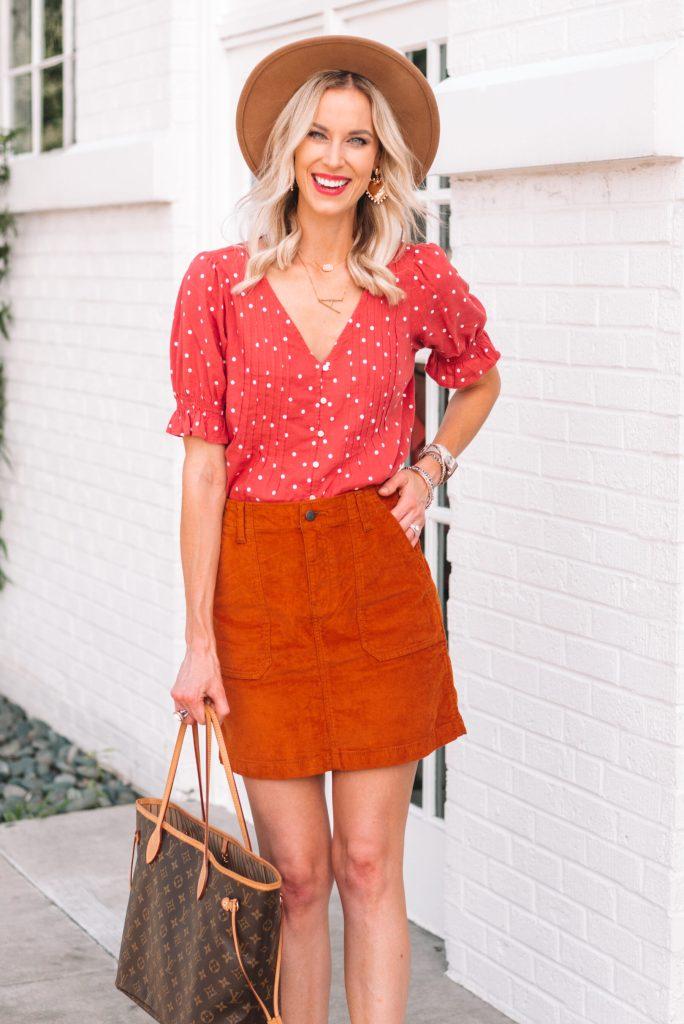 burnt orange corduroy skirt with reddish pink polka dot top and hat for fall