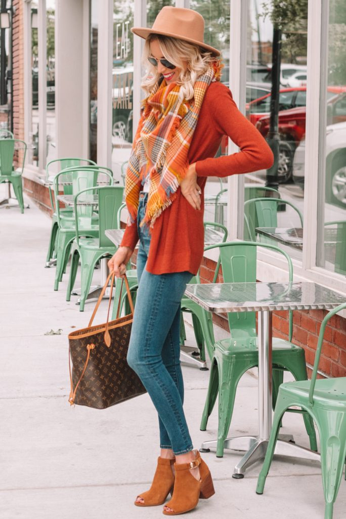 rust colored cardigan, blanket scarf, and jeans for a Thanksgiving outfit idea
