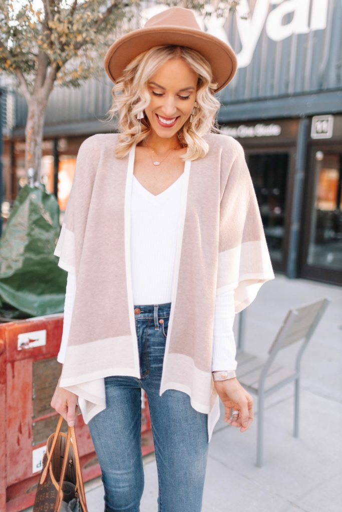 neutral poncho wrap for fall styled with white v-neck t-shirt and hat