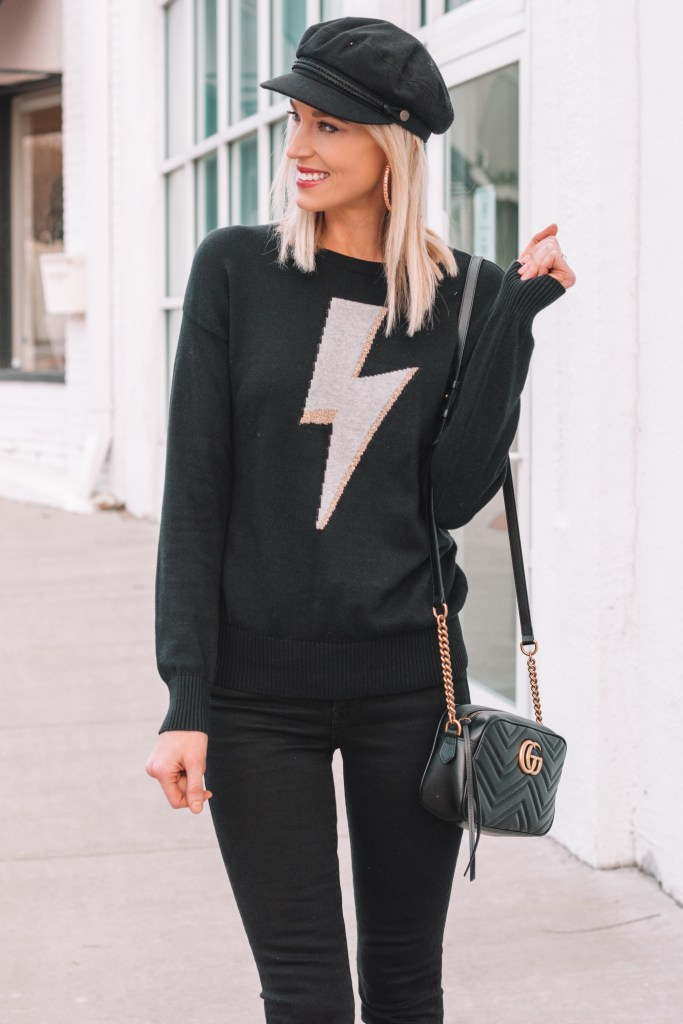 lightening bolt sweater, black jeans, black hat