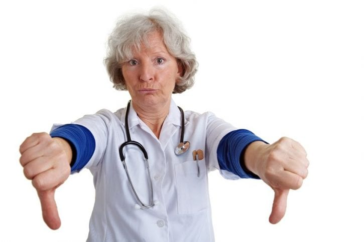 9108639 - elderly female doctor holding her two thumbs down