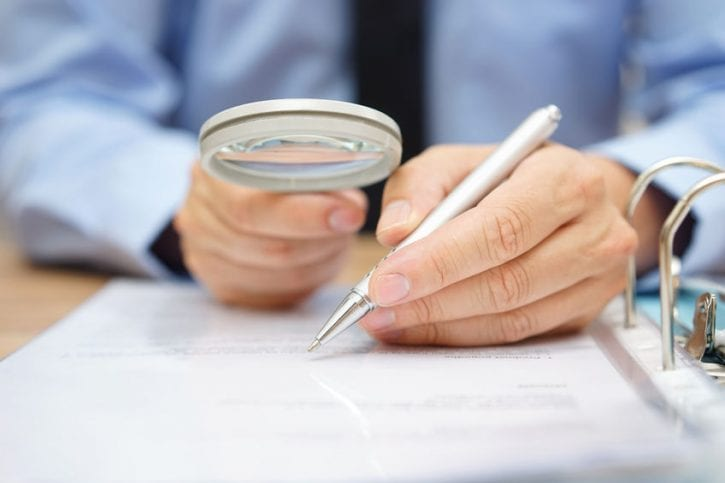 47708393 - businessman is analyzing  through  magnifying glass contract and prices