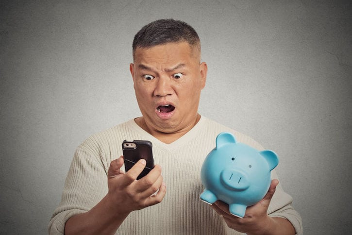 37960087 - portrait shocked man looking at his smart phone holding piggy bank