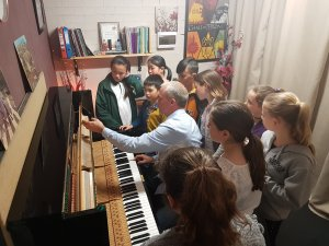 A group of students looking at a Piano being taken apart by their class tutor. The tutor has a piano key in his hand and is showing the students the anatomy of the Piano.