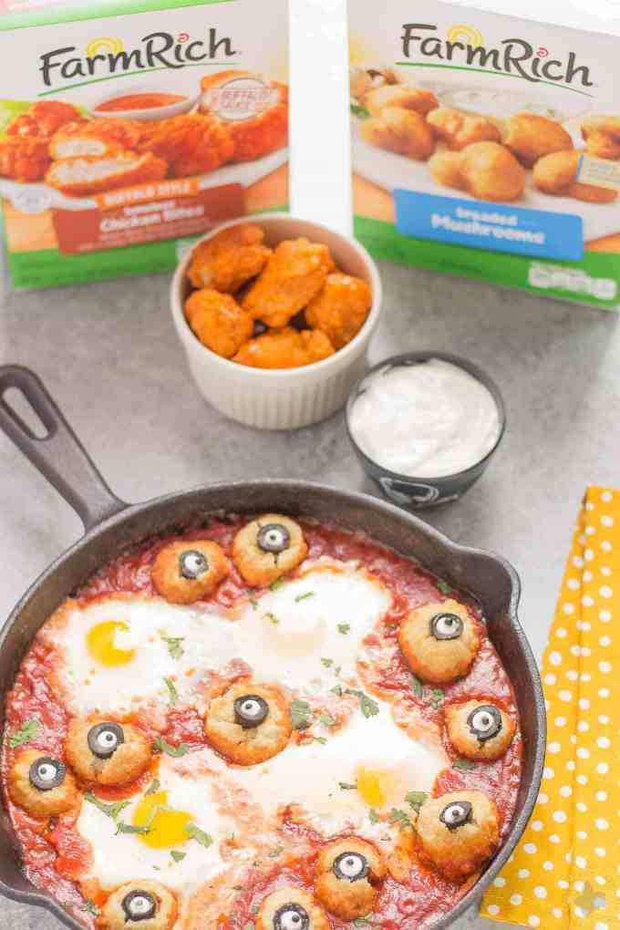 Eggs are baked in a tomato sauce and then breaded mushrooms with sliced black olives, made to looks like eyes, are nestled alongside to create this Halloween Eyeball Skillet. A festive meal sure to please the entire family! | Strawberry Blondie Kitchen