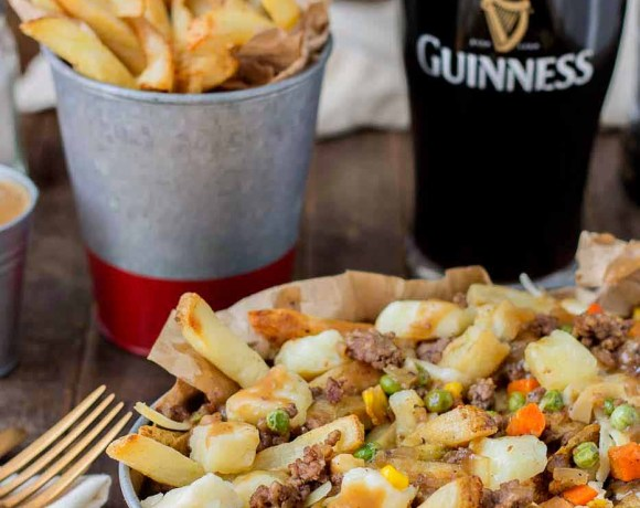 Crispy fries piled high with beef and mixed vegetables, smothered in Guinness gravy and topped with cheese curds make for one awesome Shepherd's Pie Poutine. | Strawberry Blondie Kitchen