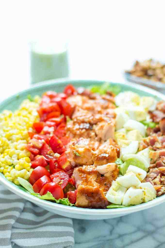 BBQ salmon cobb salad with Avocado Ranch Dressing is bursting with flavors to savor summer! Topped with a delicious crunch from ranch flavored chickpeas it's sure to be your next favorite salad! | Strawberry Blondie Kitchen