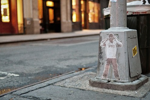 a small wheatpaste of a man wearing a nyc baseball hat and jersey on a lamp pole in SoHo, NYC