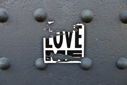 A sticker by street artist love me