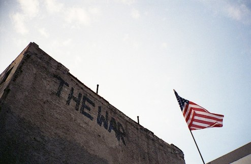 an american flag and the war graffiti by a gas station in the lower east side of NYC
