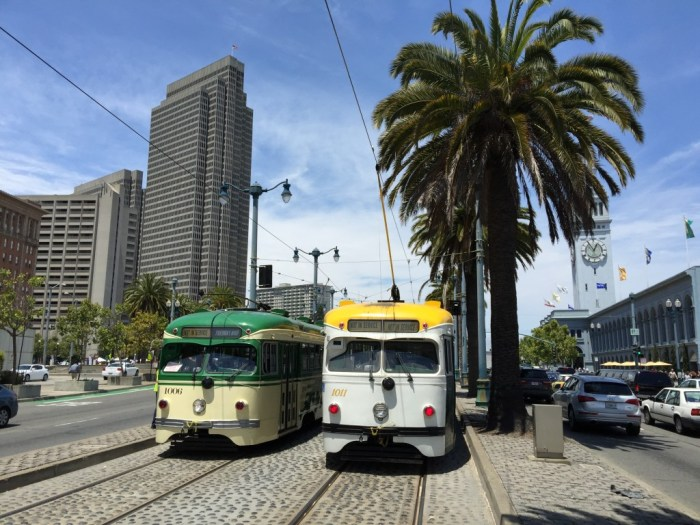 Vintage 1948 double-end PCC streetcars Nos. 1006 (left) and 1011 pass just south of the Ferry Building during E-line training, July 1, 2015