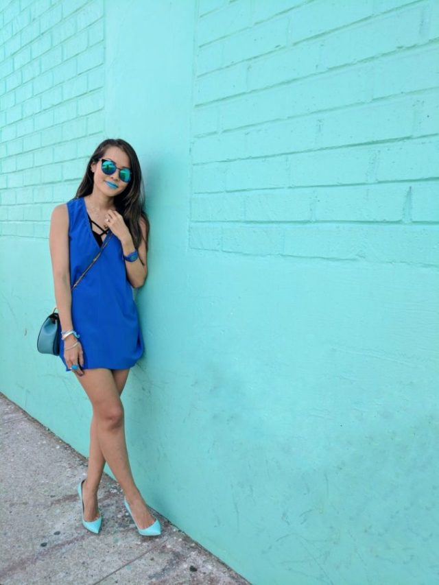 girl standing in front of tiffany blue wall
