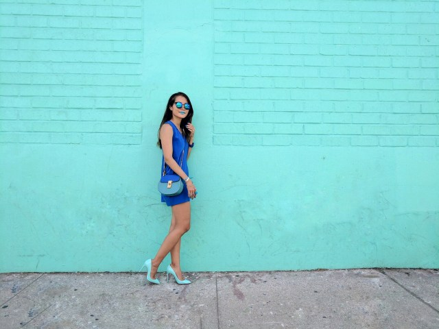 girl in blue standing in front of teal wall