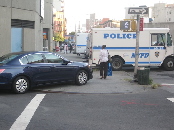 One of many cars parked on the sidewalk, this one blocks the crosswalk. Photo: Noah Kazis.
