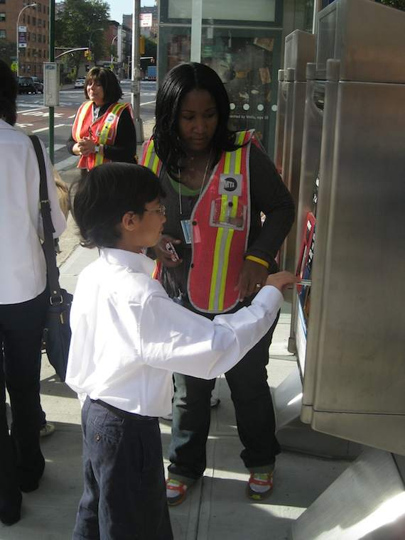 An MTA employee helps a school-bound child learn how to pay his bus fare before boarding. He didn't have any trouble. Photo: Noah Kazis.