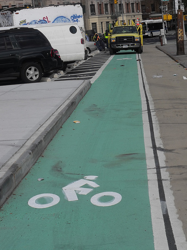 DOT workers installing the one block-long contraflow bike lane on St. Nicholas. Photo: BicyclesOnly via Flickr.