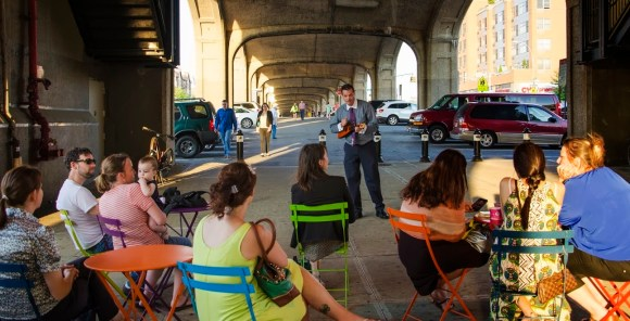 Roberto Buscarsi plays during Make Music New York at 40th Street and Queens Boulevard. The parking in the background will remain, but space beneath the elevated 7 train in Sunnyside is set for some plaza improvements. Photo courtesy Sunnyside Shines BID