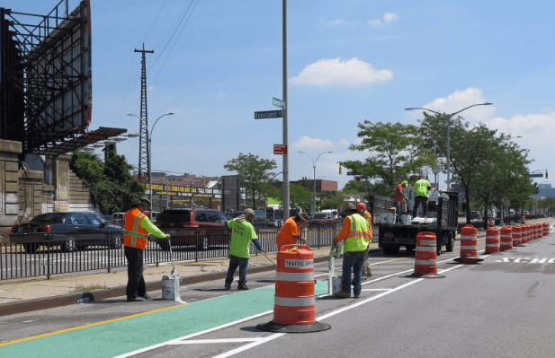 DOT crews installing the new protected bike lane earlier this month at Kneeland Street. Photo: DOT
