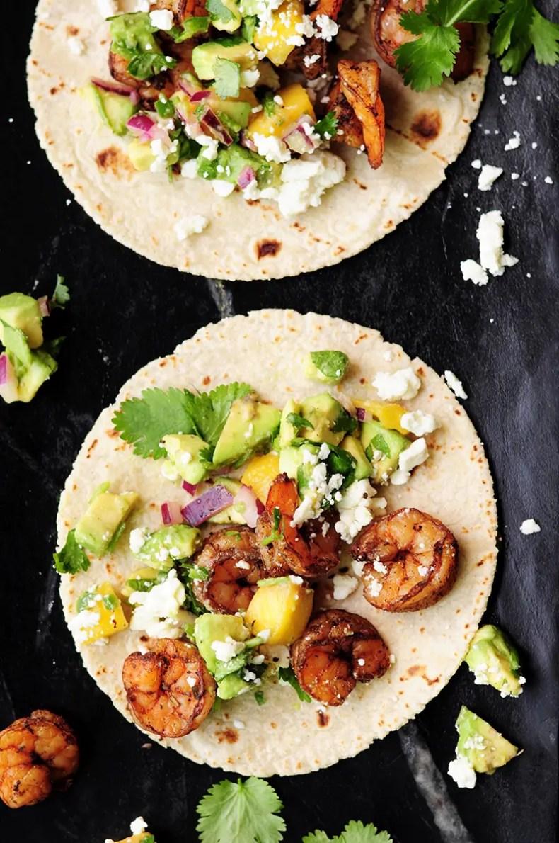 Shrimp tacos made with a homemade blackened seasoning mix, topped with refreshing mango avocado salsa and feta cheese. Yum!