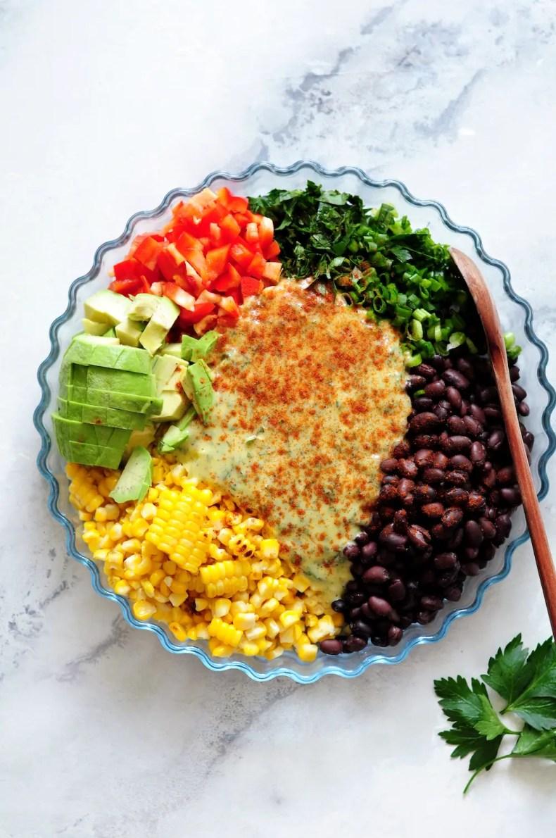 Corn and Black Bean Salad ingredients with garlic lemon aioli on top