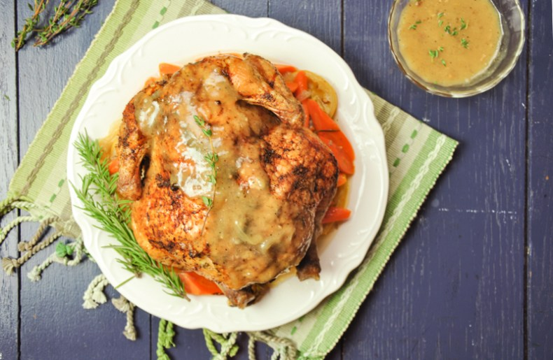 A whole chicken stuffed with herbs sits on top of a savory white wine broth with carrots, onion, and lemon, creating a delicious gravy while roasting.