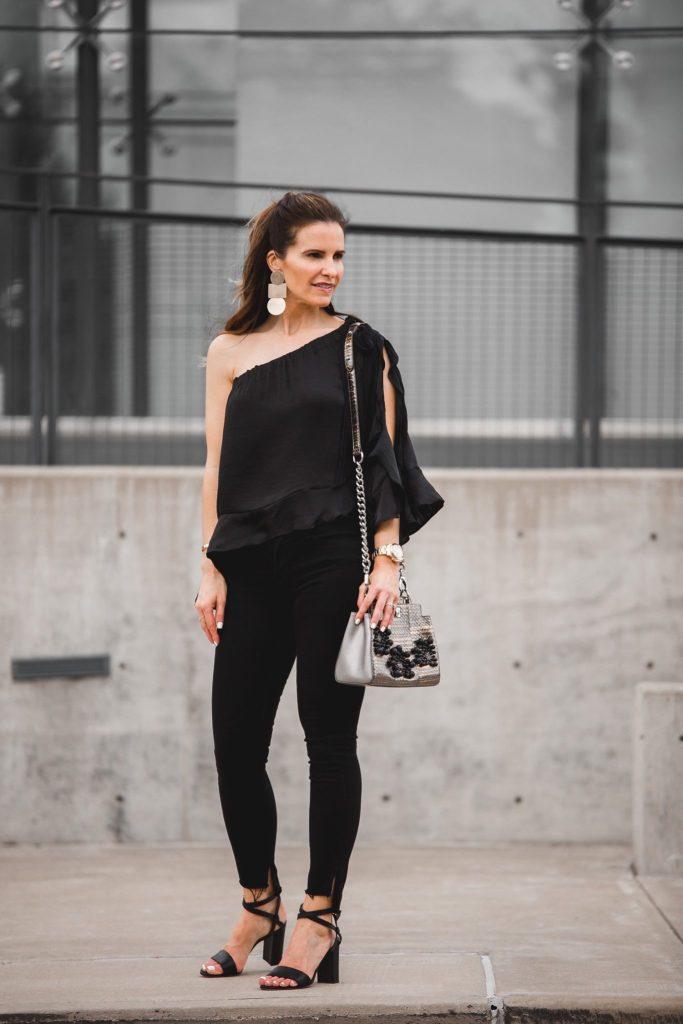 black silk one shoulder top// black jeans// gold drop earrings// silver handbag// black strappy heels