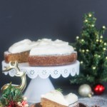 A slice of Spiced Fennel Cake with Eggnog Whipped Cream served in front of the full cake