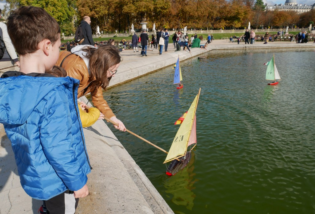 Sailing wooden boats in Luxembourg Gardens Paris with children.s