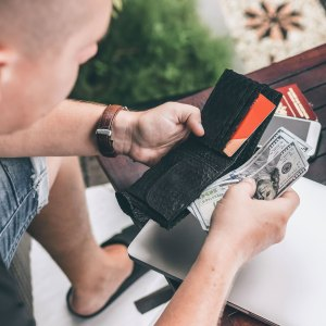 A man pulling money out of his wallet