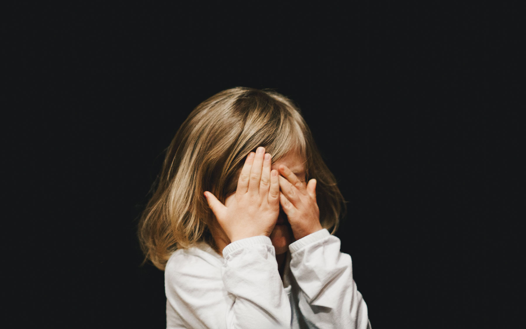 A little girl covering her eyes