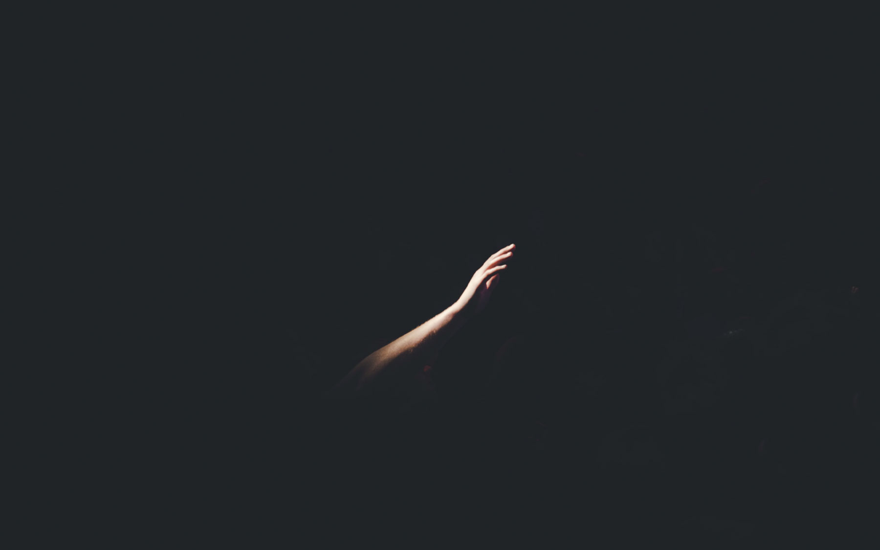 A hand reaching out in the darkness