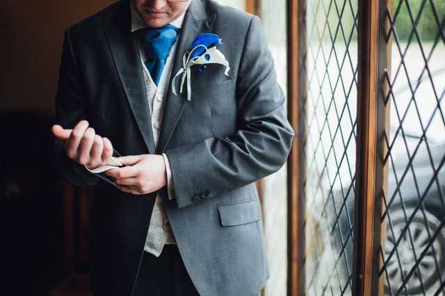 groom fixing cufflinks