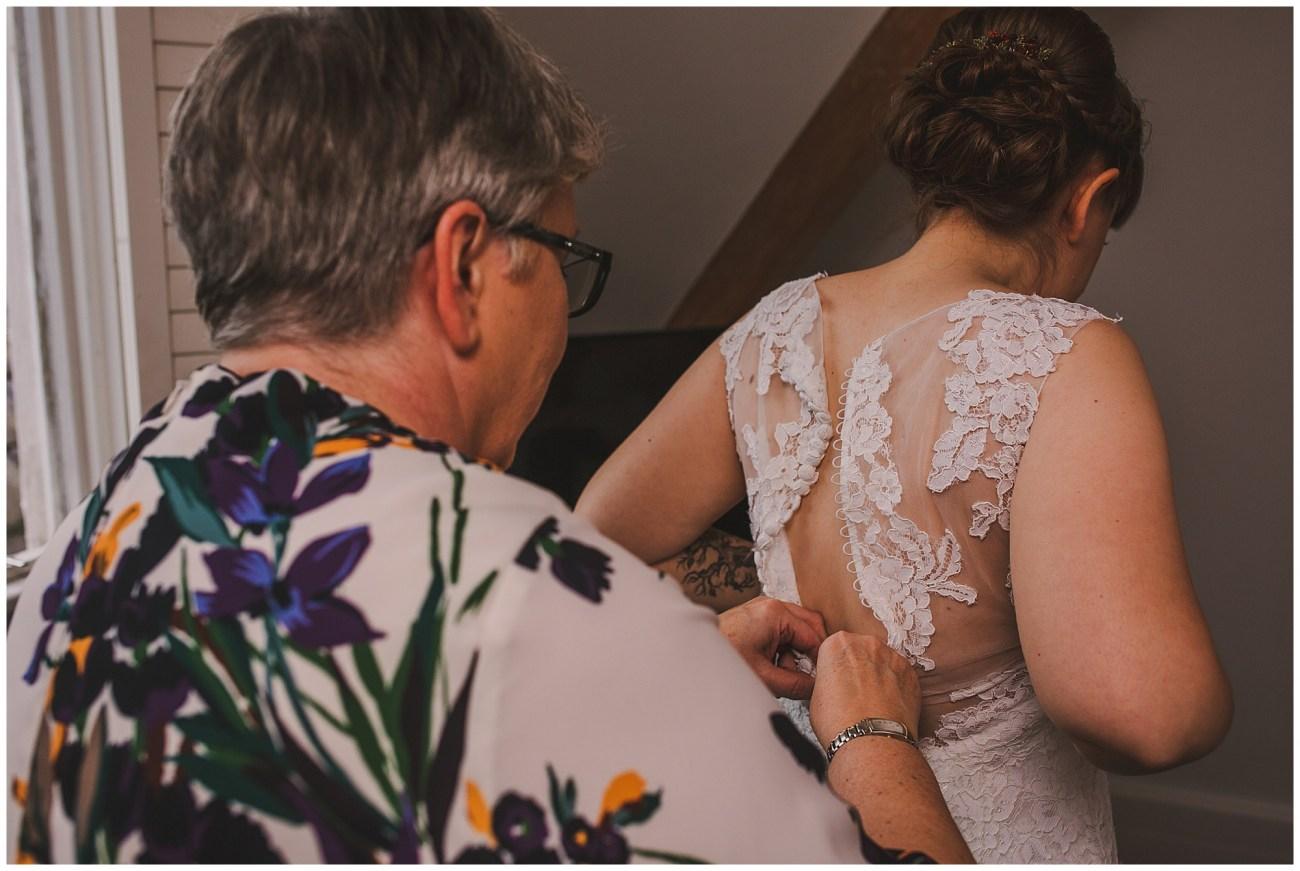 mother zipping brides dress