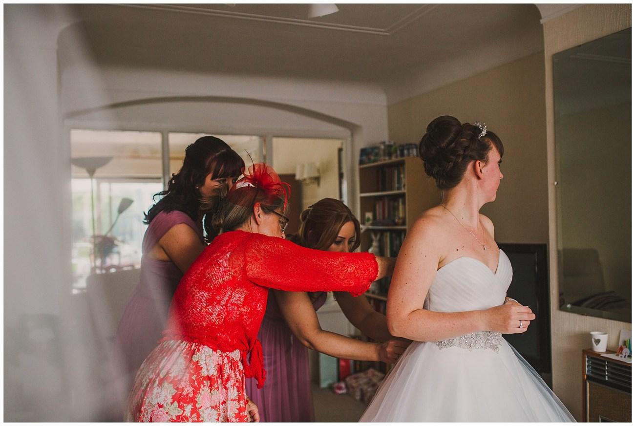 mum and bridesmaids doing up brides dress