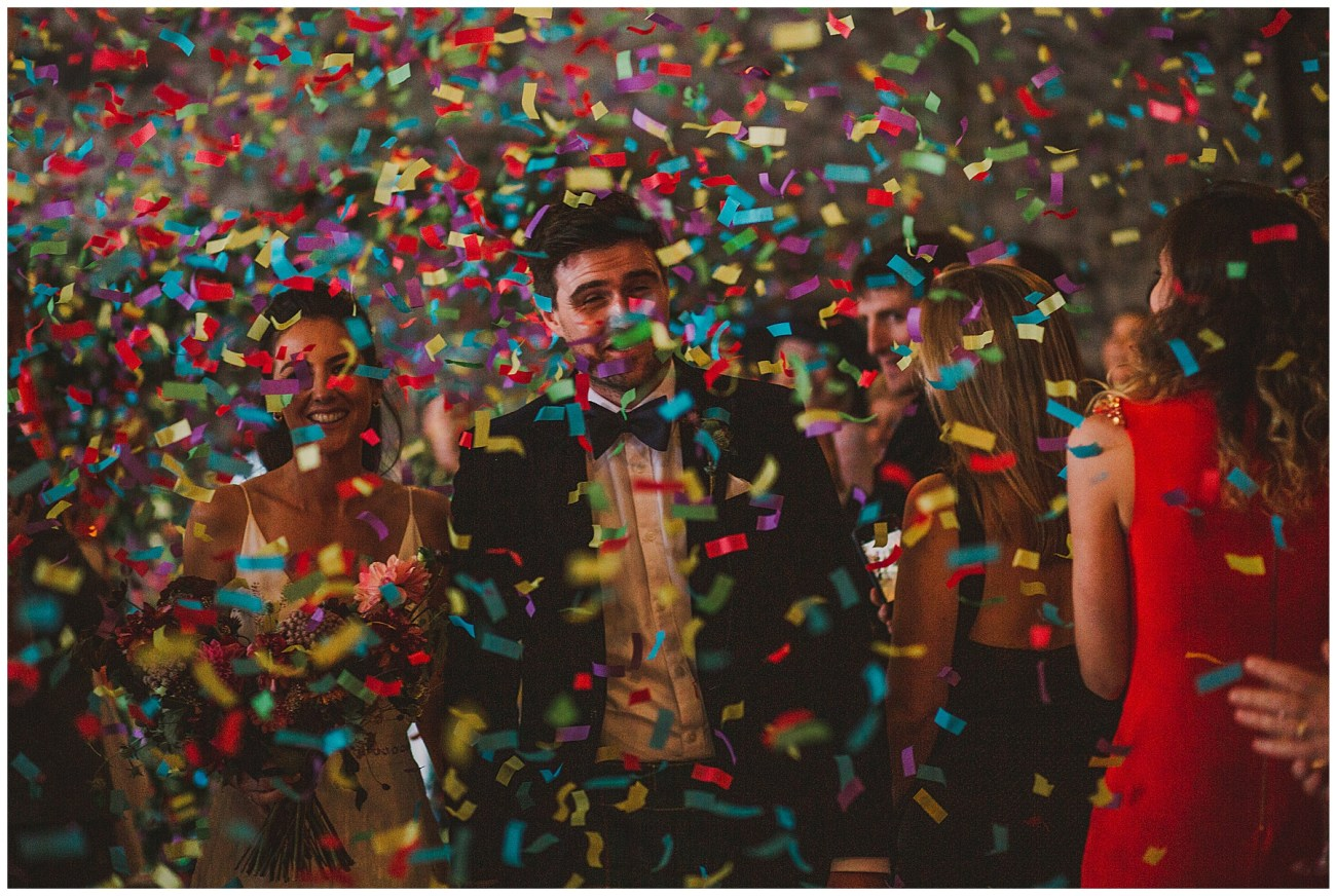 bride and groom covered by confetti