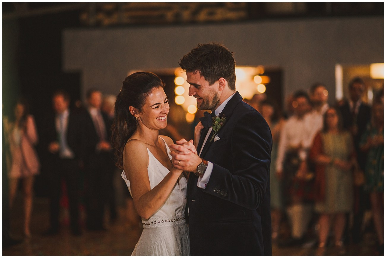 bride laughing whilst dancing with groom