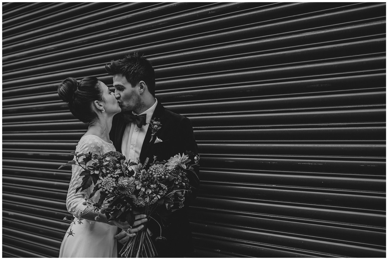 bride and groom kissing by shutters black and white