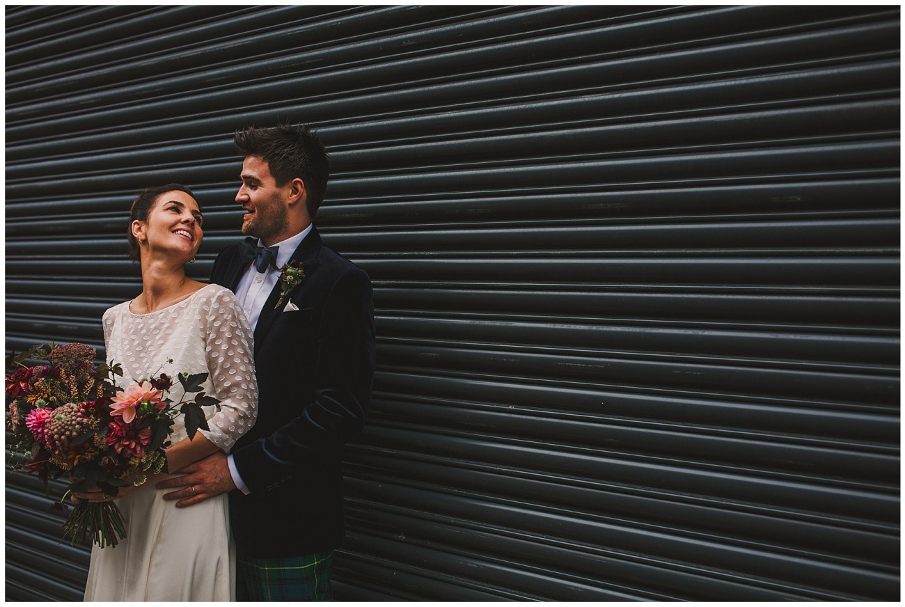 bride and groom smiling in front of shutters and cuddling