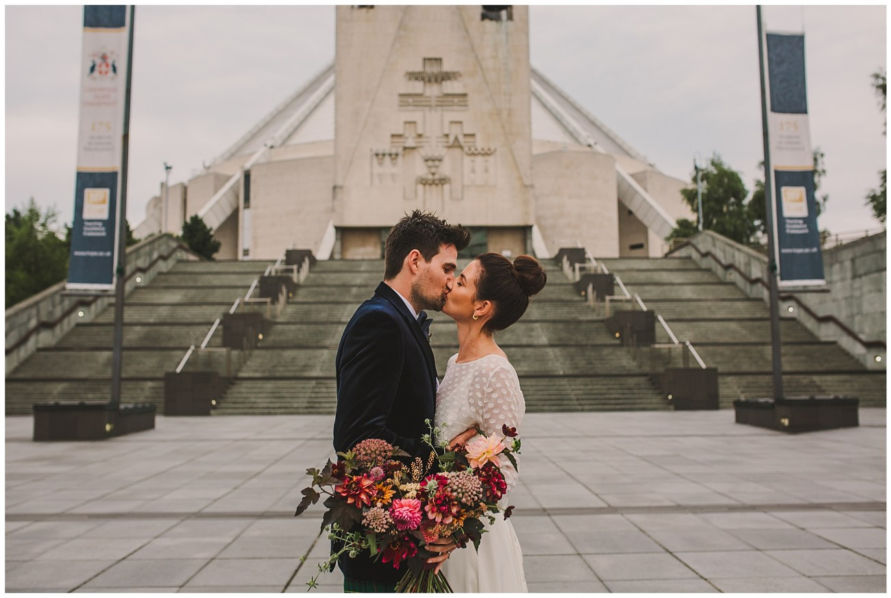 bride and groom kissing in front of liverpool metropolitan cathedral