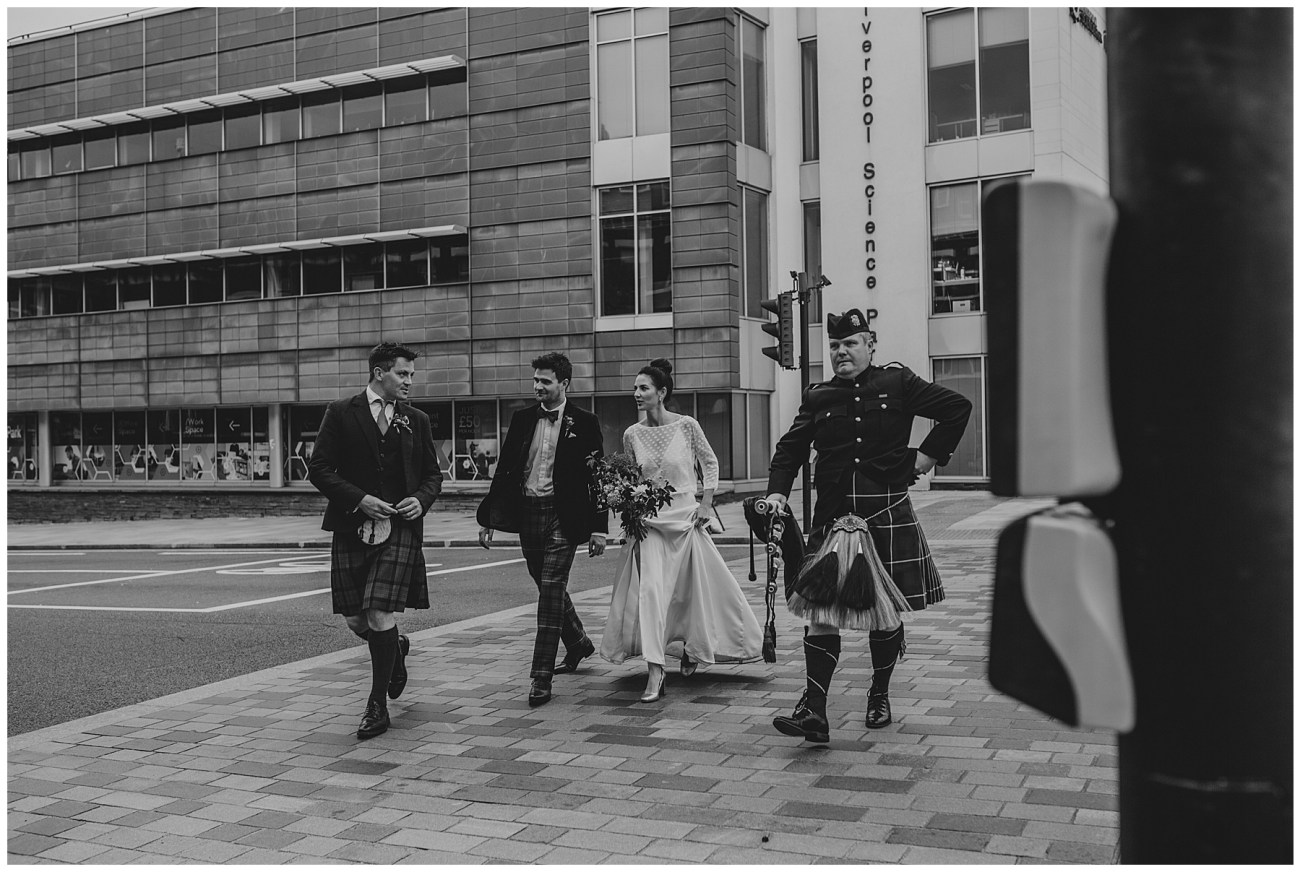 bride and groom walking with bagpiper