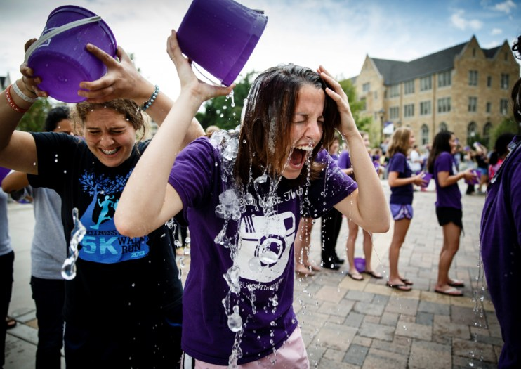 """Students Jenny Murtha (right) and Sarah Rae LaValla douse themselves with ice water as part of UST's mass """"Ice Bucket Challenge."""""""