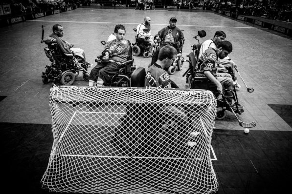 Players fight for the ball in front of the net during the Minnesota Saints PowerHockey Cup game against the Calgary Selects on July 21 at The Legendary Roy Wilkins Auditorium in downtown St. Paul. PowerHockey is a sport for disabled athletes with rules similar to hockey. Several UST alums play and coach in the PowerHockey League.