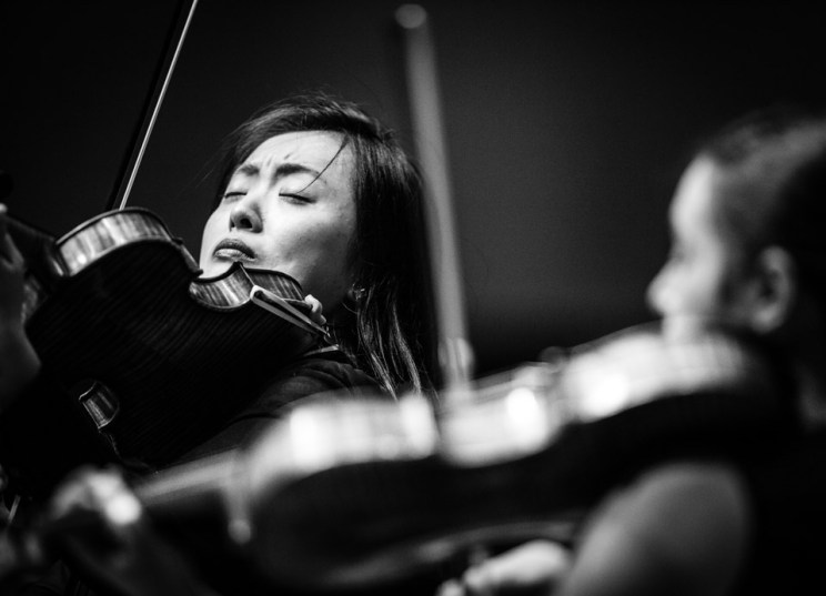 Ying Xue plays violin in the Chapel of St. Thomas Aquinas during a Parker Quartet performance.