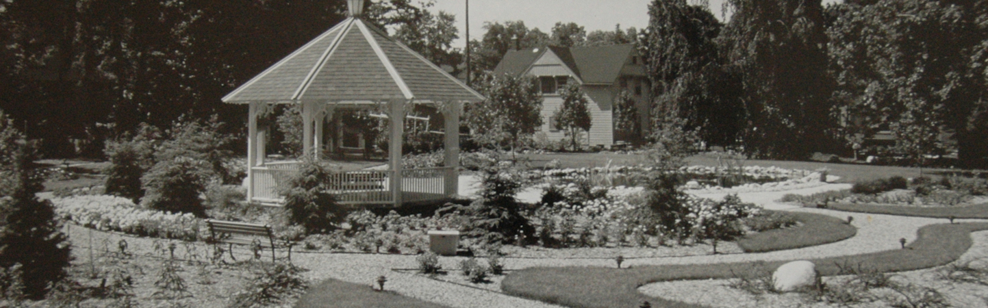Black and white photo of wooden gazebo in manicured garden with bed of annuals and crushed stone pathways.