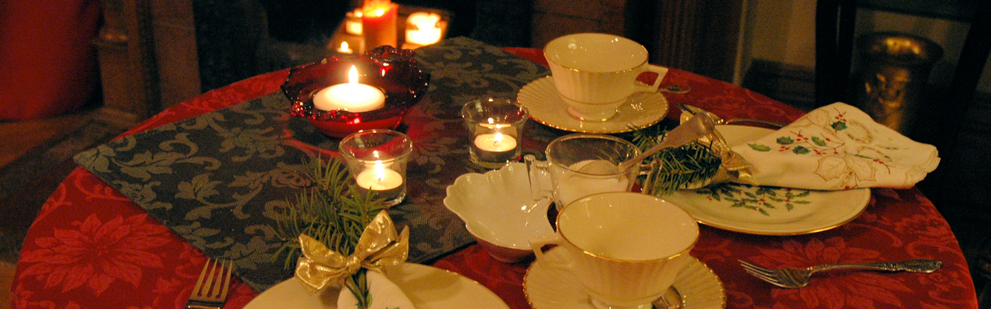 Table for two set for Christmas Tea with red damask cloth, linens embroidered in green and red, creamy Lennox China, silver, candles, and fresh greenery.