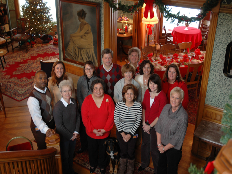 Office staff gathers mid holiday greenery, berries and bows at Stuart Avenue BnB