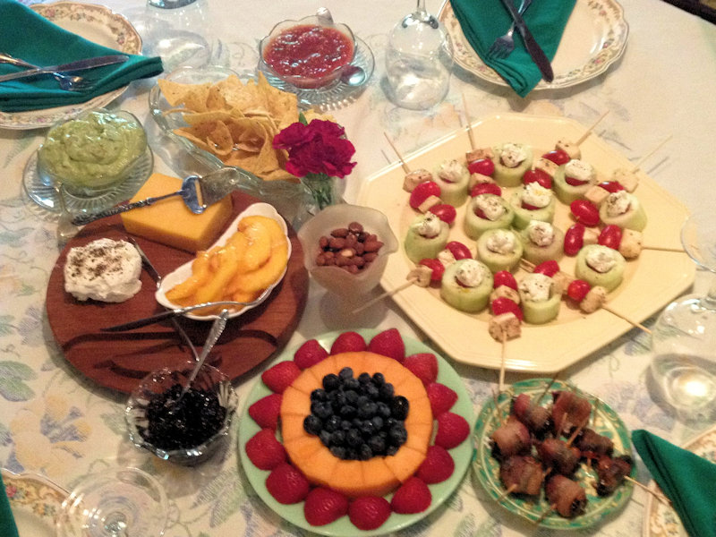 Assorted plates of cheese, fresh fruit, nuts, bacon-wrapped dates, tomato-cucumber skewers laid out on a vintage tablecloth with vintage dishes and napkins