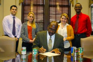 "President Rodney D. Bennett signs a proclamation designating Nov. 18-23 as ""Let's SAAC Hunger"" week on the USM campus. Courtesy photo"