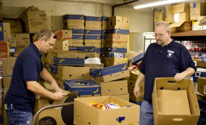 Staff members of the Hattiesburg homeless shelter Jim Prout and Bert Kilgore package and organize boxes of food to give out to those in need.  Hunt Mercier / Printz